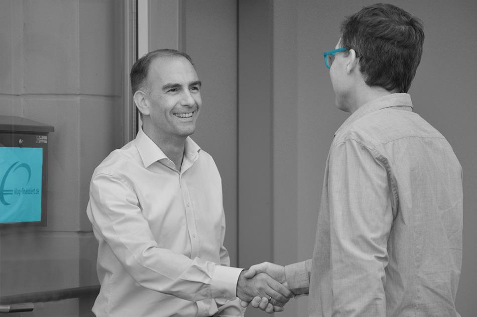 Baufinanzierungs-Berater nimmt Kunden in Empfang